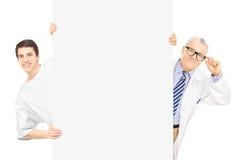 El paciente y el centro masculinos jovenes envejecieron al doctor que se colocaba detrás del panel Imagenes de archivo