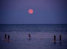 El paddleboarding de pie debajo de la Luna Llena imagen de archivo