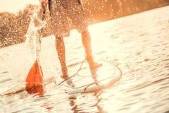 El paddleboarding de pie del hombre imagenes de archivo