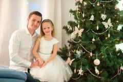 El padre abraza a la hija cerca del árbol de navidad el víspera de Navidad Fotografía de archivo libre de regalías