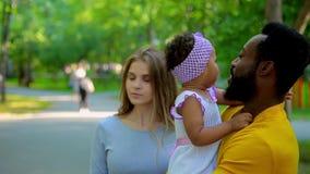 El padre afroamericano mira cariñosamente a su pequeña hija con amor metrajes