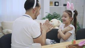 El padre alegre está jugando con su hija Están jugando con sus manos agradables e interesantes, el juego infantil
