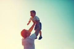 El padre alegre feliz de la foto de color del vintage lanza para arriba al niño Fotografía de archivo libre de regalías