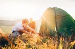 El padre aprende su tienda de campa?a puesta hijo en el claro del bosque de la puesta del sol imagen de archivo