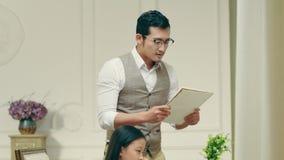 El padre asiático mira qué hija ha escrito o ha dibujado metrajes