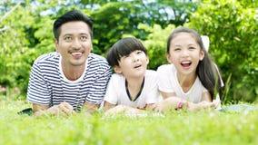 El padre asiático y sus niños mienten en el libro de la historia de la lectura del prado almacen de metraje de vídeo