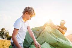 El padre ayuda a su tienda del ajuste del hijo en el claro del bosque de la puesta del sol foto de archivo