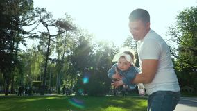 El padre balancea a su poca hija en sus brazos en parque del verano con la llamarada de la lente almacen de metraje de vídeo