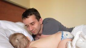 El padre besa al hijo que duerme en la cama El bebé es menos de dos años almacen de metraje de vídeo