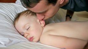 El padre besa al hijo que duerme en la cama El bebé es menos de dos años Primer metrajes