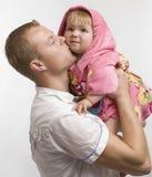 El padre besa a su pequeña hija del bebé