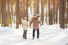 El padre camina con sus pequeños hijas y adolescente-hijo en un bosque en invierno Imágenes de archivo libres de regalías