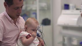 El padre cariñoso detiene a su pequeña hija en brazos en el hospital metrajes