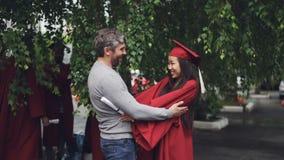 El padre cariñoso está felicitando a su hija el día de graduación, la gente es de abrazo y de risa al aire libre mientras que otr metrajes