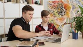El padre caucásico ayuda a su hijo a imaginar con su hometask usando la cámara lenta del ordenador portátil almacen de metraje de vídeo