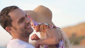 El padre coge a la niña en sombrero en el mar en lento