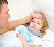 El padre comprueba temperatura del daugher enfermo con su mano Foto de archivo libre de regalías