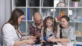 El padre con dos hijas en una recepción en el terapeuta de la oficina del doctor con sonrisas considera la radiografía almacen de video