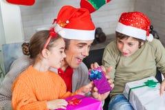 El padre con dos niños abre regalos de Navidad Imágenes de archivo libres de regalías
