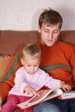 El padre con el bebé leyó el libro Imágenes de archivo libres de regalías