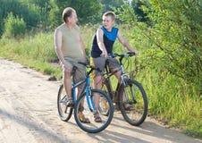 Dos hombres en bicicletas en el camino rural en el día soleado del verano Imagen de archivo libre de regalías