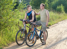 Para hombre en bicicletas en el camino rural en el día soleado del verano Fotos de archivo libres de regalías