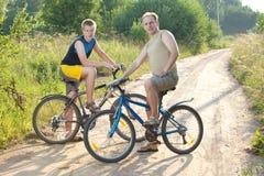 El padre y el hijo en bicicletas en el camino rural en el día soleado del verano Foto de archivo