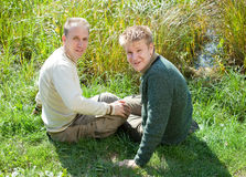 El padre con el hijo se sienta en la costa herbosa del lago Foto de archivo libre de regalías