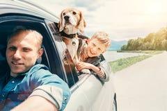 El padre con el hijo y el perro miran de la ventanilla del coche Imagen de archivo libre de regalías