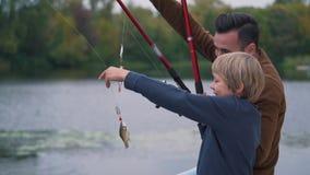 El padre con el hijo está pescando metrajes