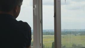 El padre con la pequeña hija en los brazos está observando un paisaje a través de la ventana almacen de metraje de vídeo