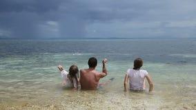 El padre con las hijas lanza los guijarros en el mar almacen de metraje de vídeo
