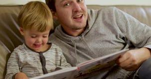 El padre con el pequeño hijo leyó el hogar del libro almacen de video