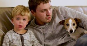 El padre con el perro del hijo está sentando el sofá almacen de metraje de vídeo