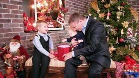 El padre da a los hijos de un regalo de la Navidad, niños que miran los regalos de padres que el buen padre pasa Nochebuena con almacen de video