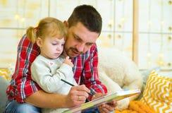 El padre de Cary enseña a la hija del niño a dibujar foto de archivo