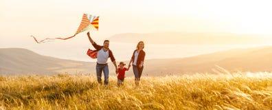 El padre de la familia, la madre y la hija felices del niño lanzan una cometa encendido Fotografía de archivo