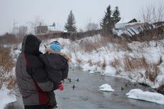 El padre de un hombre se coloca con el suyo que retiene a un pequeño niño en sus brazos que miran el río en invierno foto de archivo libre de regalías