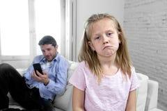 El padre del adicto a Internet que usaba el teléfono móvil que ignoraba a la pequeña hija triste agujereó solo y deprimido foto de archivo libre de regalías