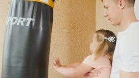 El padre detiene a una pequeña hija en las manos y la muchacha linda está batiendo por el punchbag almacen de metraje de vídeo