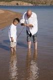 El padre enseña al hijo a pescar Fotos de archivo