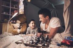 El padre enseña pequeño hijo a cómo jugar a ajedrez en la noche en casa imagen de archivo libre de regalías