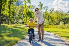 El padre enseña su paseo del hijo a una bicicleta foto de archivo