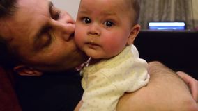 El padre está besando seis meses del bebé pero él no goza de él Padre e hijo que pasan una cierta hora de la calidad junta almacen de metraje de vídeo