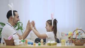 El padre está enseñando a su hija a jugar a un juego Están jugando con sus manos agradables e interesantes, el juego infantil