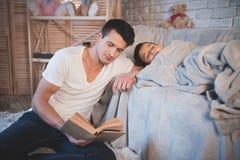 El padre está leyendo cuentos de hadas reserva a su hijo durmiente en la noche en casa Fotografía de archivo