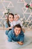 El padre feliz con el bebé en sus hombros está mintiendo en la Tulle mientras que la madre está abrazando al bebé Imagen de archivo libre de regalías