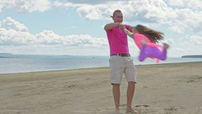 El padre feliz de la familia da vuelta al hijo del bebé en la playa