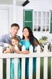 El padre feliz, la madre y la pequeña hija se colocan al lado de la cerca Fotos de archivo libres de regalías