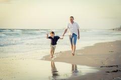 El padre feliz que juega en la playa con el pequeño funcionamiento del hijo emocionado con descalzo adentro enarena y riega Fotografía de archivo